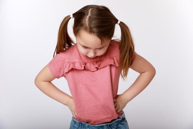 Bambina emotiva offesa con due code di cavallo con le mani in vita