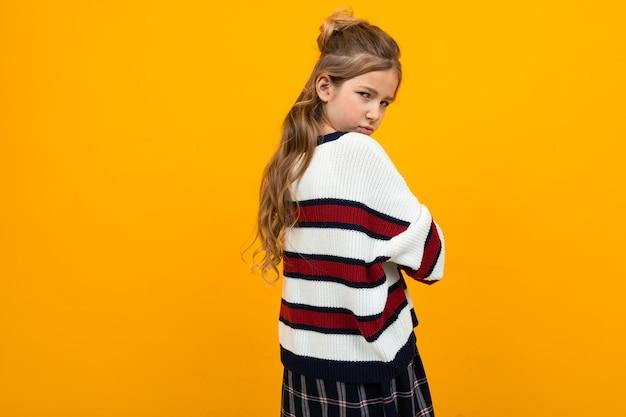 Ragazza adolescente triste offesa in un maglione a righe con le braccia incrociate su uno sfondo arancione con spazio di copia.