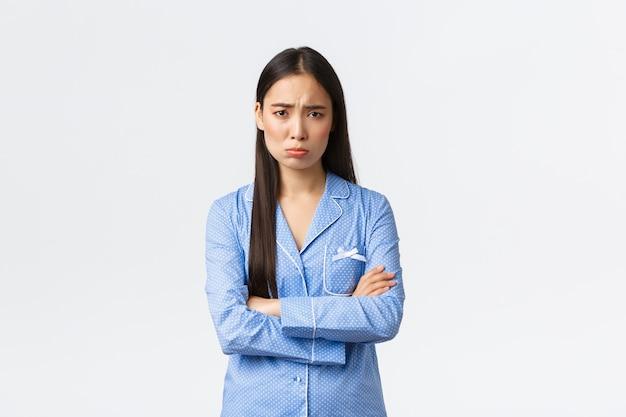 Offeso stupido insicura ragazza asiatica in pigiama blu, mani incrociate sul petto e singhiozzando, imbronciato e accigliato dalla situazione ingiusta, sentirsi insultato e triste, in piedi timido su sfondo bianco