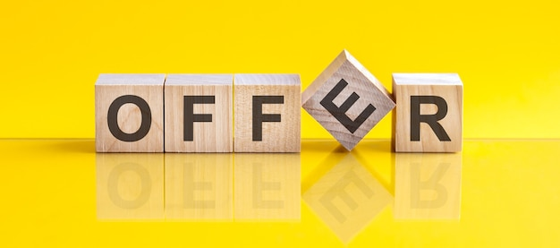 Offerta parola scritta sul blocco di legno. la parola offerta è fatta di blocchi di legno che si trovano sul tavolo giallo. concetto di business
