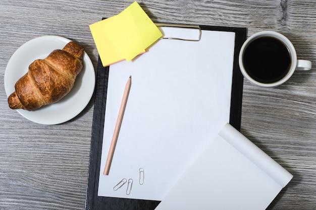 Accessori per ufficio su tavolo grigio in legno: appunti, tazza di caffè, croissant fresco