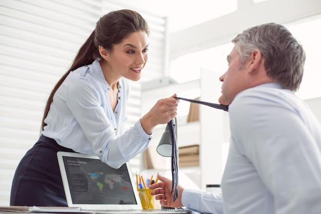 Nell'ufficio. attraente bella giovane donna in piedi di fronte al suo collega e parla al suo mentre si tiene la cravatta