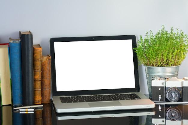 Desktop in vetro nero per ufficio con computer, fiori e forniture