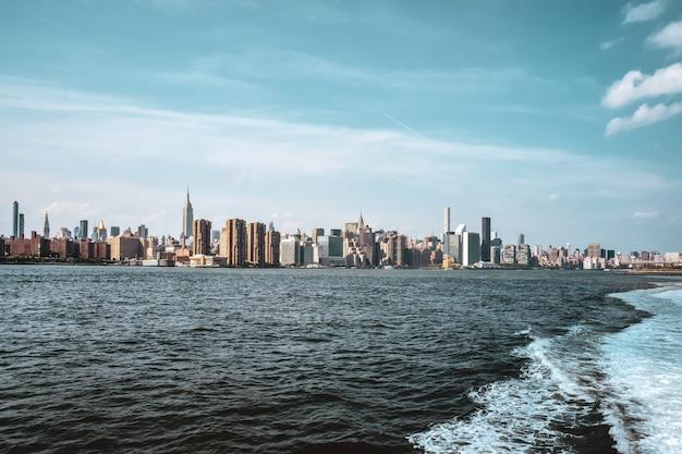 Edifici per uffici e appartamenti sullo skyline al tramonto, dal fiume hudson. immobiliare e concetto di viaggio. manhattan, new york city, stati uniti.