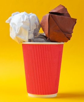 Concetto di business ufficio. palle di carta in tazza di caffè sul tavolo giallo.