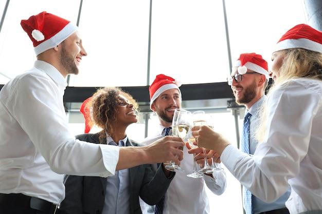 Colleghi di affari dell'ufficio che celebrano le vacanze invernali insieme al lavoro e bevono champagne in ufficio. buon natale e felice anno nuovo.