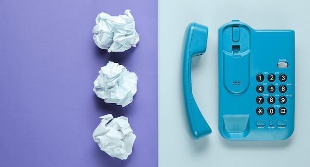 Concetto di minimalismo aziendale di office. telefono dell'ufficio, palline di carta sgualcite su carta colorata