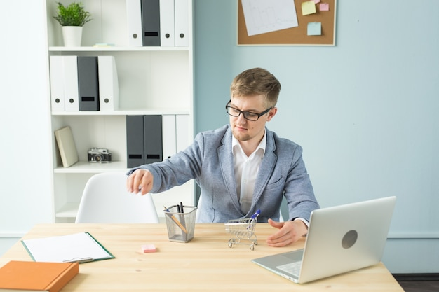 Ufficio, uomini d'affari, concetto di pausa - il manager sta giocando con il carrello del supermercato giocattolo in ufficio