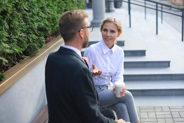 Colleghi d'ufficio che parlano all'aperto per le strade della città, facendo una pausa caffè seduti su una panchina.
