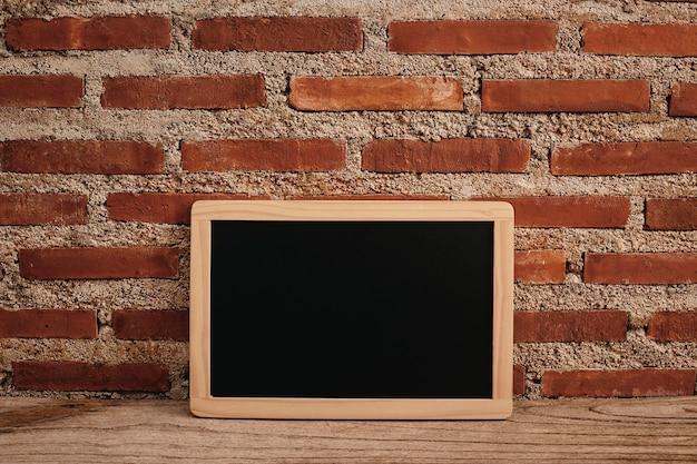 Scrivania creativa da ufficio con lavagna sulla tavola di legno e muro di mattoni bianchi