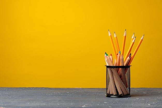 Tazza da ufficio con matite e articoli di cancelleria su sfondo giallo vista frontale