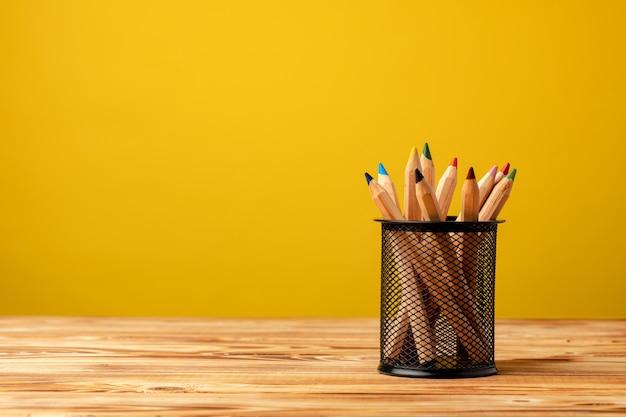 Tazza da ufficio con matite e articoli di cancelleria su sfondo giallo