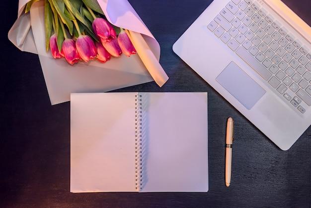 Scrivania da ufficio e bouquet di tulipani vista dall'alto