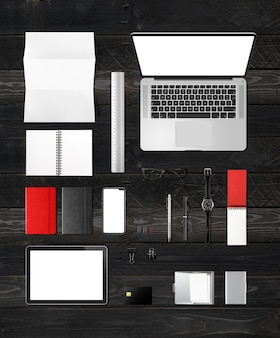 Scrivania da ufficio branding mockup vista dall'alto isolato su fondo di legno nero. spazio bianco