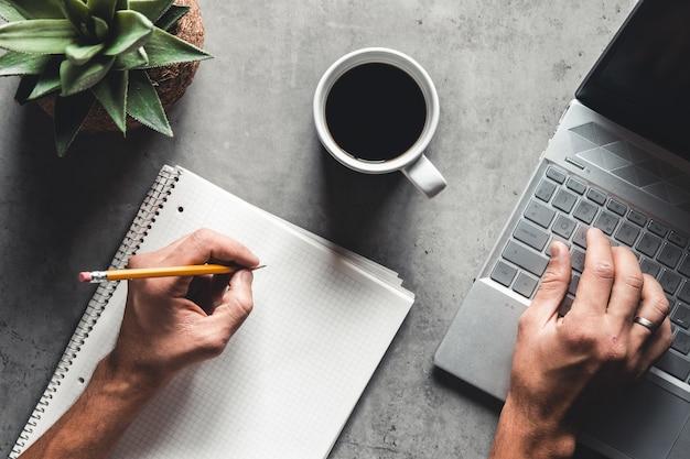 La vista piatta della scrivania da ufficio con laptop, mouse, albero, graffetta, tazza di caffè, taccuino, matita, occhiali neri su sfondo bianco.