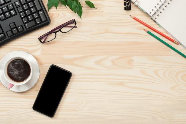Scrivania da ufficio distesa con caffè caldo, taccuino e pianta. lay piatto