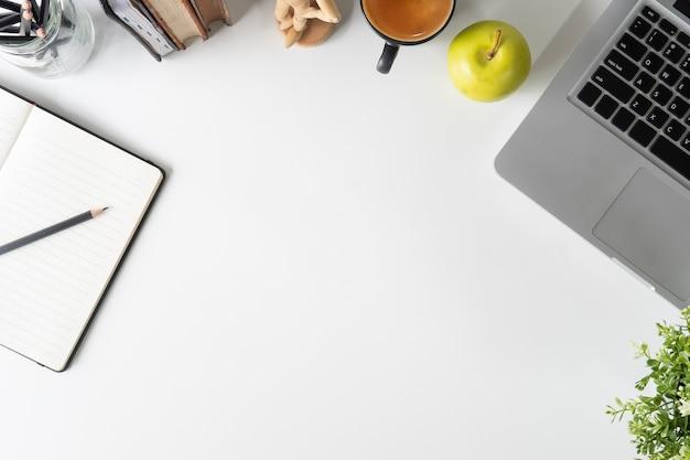 Computer portatile della scrivania, carta del taccuino, matita, libro e caffè sull'area di lavoro bianca della tavola.