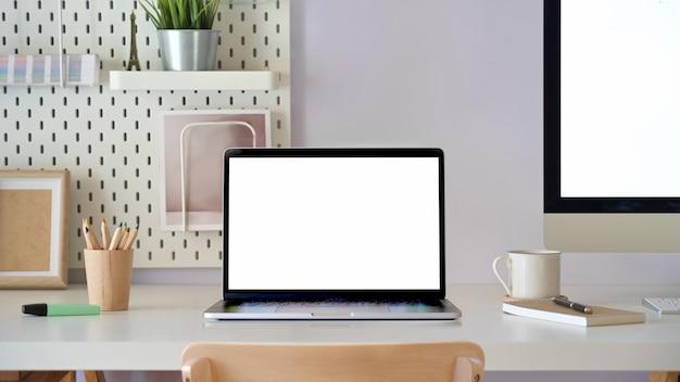 Scenario della scrivania con il computer portatile dello schermo in bianco del modello. area di lavoro minima