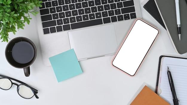 Smartphone da scrivania, computer portatile, occhiali, tazza di caffè, foglietto adesivo e taccuino.