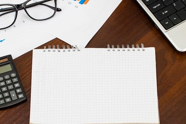 Tavolo scrivania con spazio in bianco, penna, relazione finanziaria e tazza di caffè