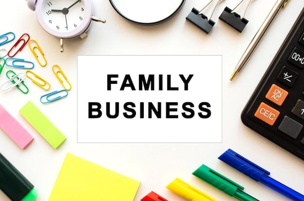 Tavolo scrivania da ufficio con penne calcolatrici e altri articoli di cancelleria testo sulla scheda family business