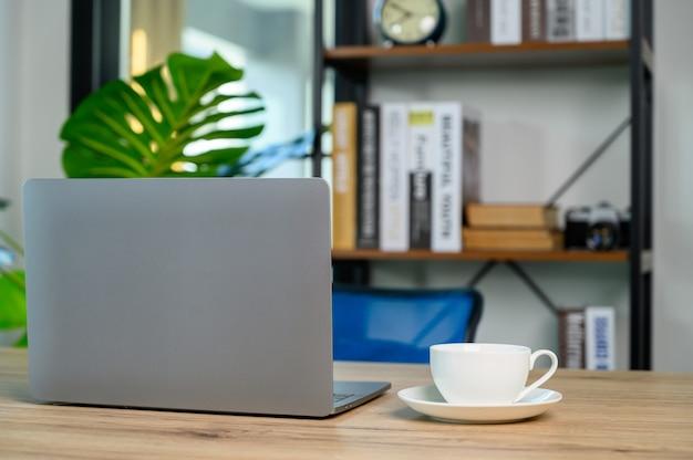 Tavolo scrivania da ufficio con computer portatile con tazza di caffè