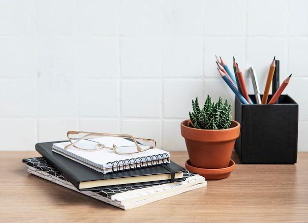 Tavolo scrivania da ufficio con quaderni, forniture e piante d'appartamento