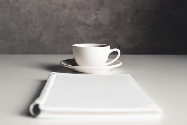 Tavolo scrivania da ufficio con forniture, tazza di caffè e fiori. vista dall'alto con copia spazio