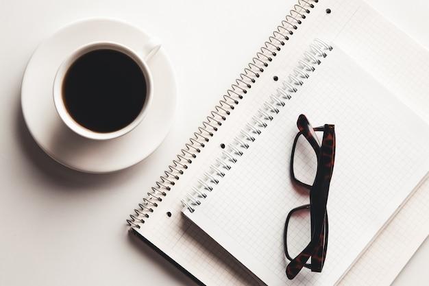 Tavolo scrivania da ufficio con forniture, tazza di caffè e fiori.