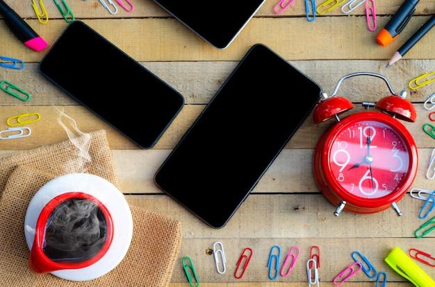 Tavolo scrivania con telefono tablet, mockup dell'area di lavoro su un tavolo di legno.