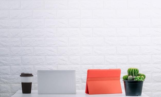 Scrivania da ufficio, computer tablet e tazza da caffè