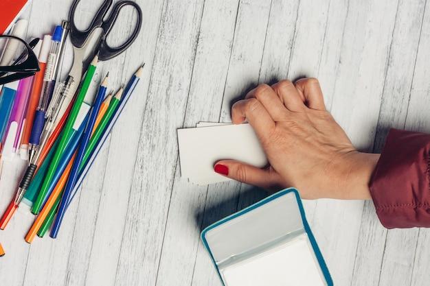 Testimonianze scrivania da ufficio e pennarelli forbici matite di cancelleria mano femminile