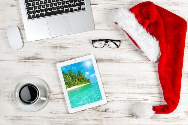 Scrivania da ufficio con caffè e decorazioni natalizie. concetto di viaggio di vacanze d'affari