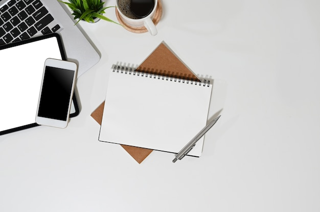 Scrivania da ufficio con un computer e un dispositivo gadget con notebook vuoto