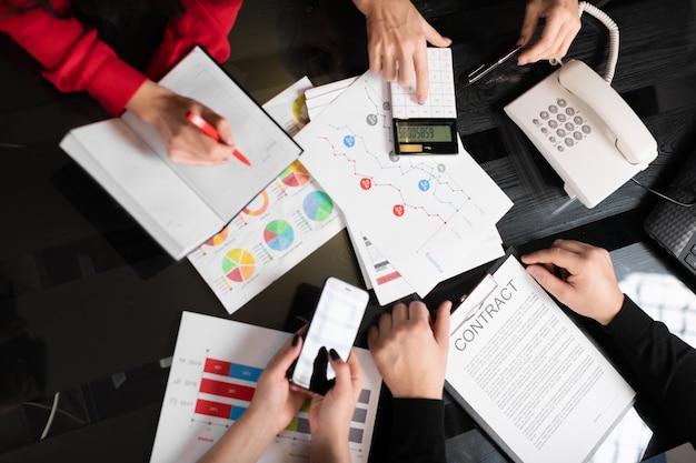 Scrivania con vista dall'alto di documenti e calcolatrice