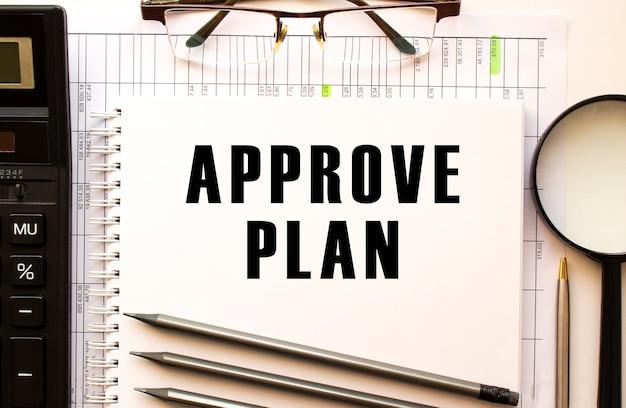 Scrivania da ufficio con documenti finanziari, lente d'ingrandimento, calcolatrice, bicchieri. pagina del blocco note con il testo approvare il piano. concetto di affari.