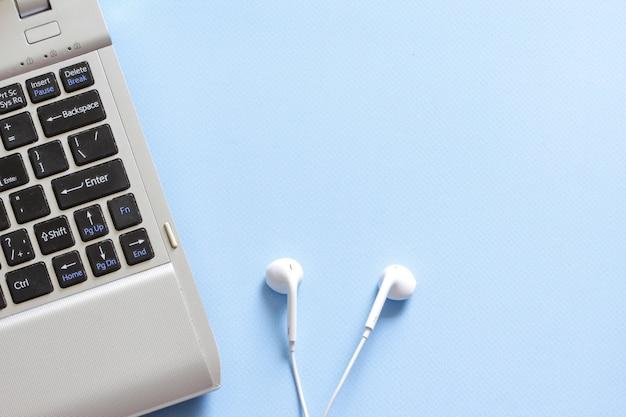 Scrivania da ufficio con auricolare e tastiera sullo sfondo rosa telelavoro operazione remota