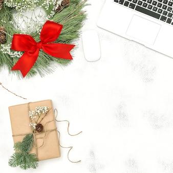 Scrivania da ufficio con laptop, ghirlanda di decorazioni natalizie e regalo incartato. lay piatto