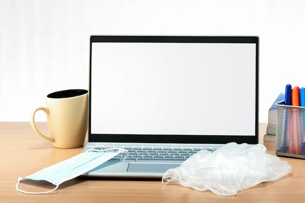 Scrivania da ufficio con laptop, maschera e guanti. luogo di lavoro protetto dal coronavirus, concetto di assistenza sanitaria.