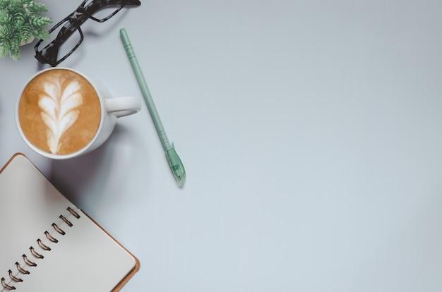 Scrivania da ufficio con taccuino, penna, caffè e albero su sfondo grigio tono vintage