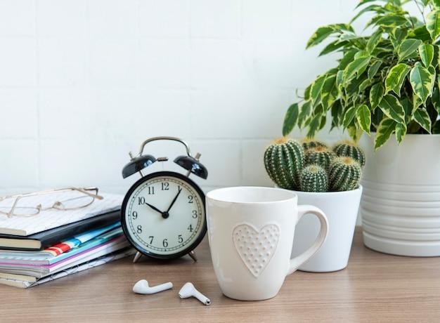 Scrivania da ufficio con una pila di taccuini, sveglia, forniture per ufficio e piante da appartamento