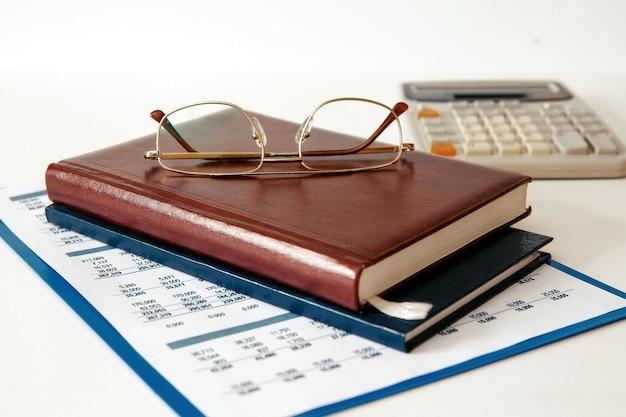 Scrivania da ufficio scrivania in legno con documenti, calcolatrice, penna, taccuino e occhiali.