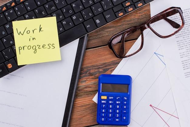 Scrivania da ufficio calcolatrice sul posto di lavoro occhiali adesivo e documenti sul tavolo di legno