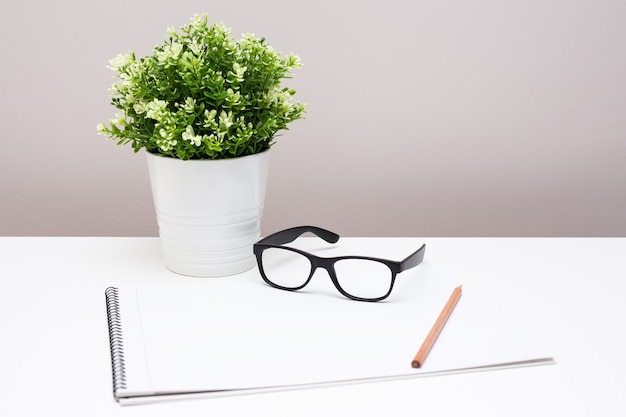Posto di lavoro scrivania con blocco note, bicchieri e fiori in vaso