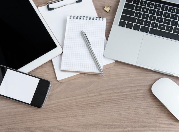 Scrivania da ufficio. computer portatile con forniture per ufficio sul tavolo.