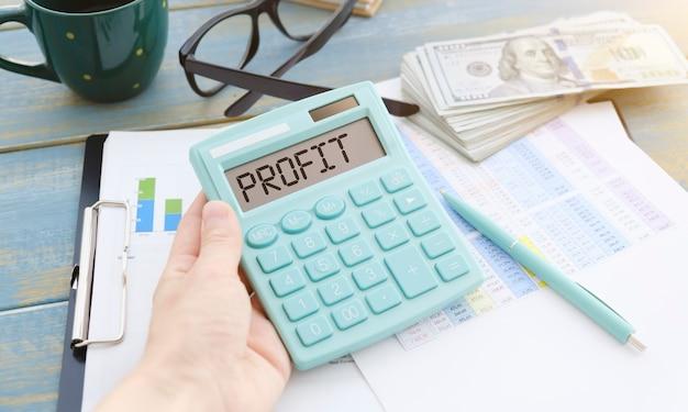 Desktop da ufficio con calcolatrice che visualizza la parola profitto. calcolo del profitto, redditività, affari, finanza o concetto di contabilità.