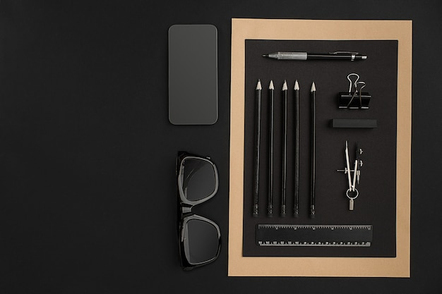 Desktop da ufficio con vari oggetti neri sullo sfondo