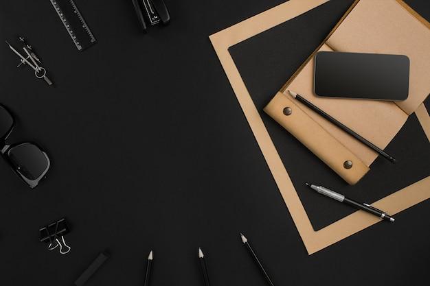 Desktop da ufficio con vari oggetti neri su sfondo nero. vista dall'alto. natura morta