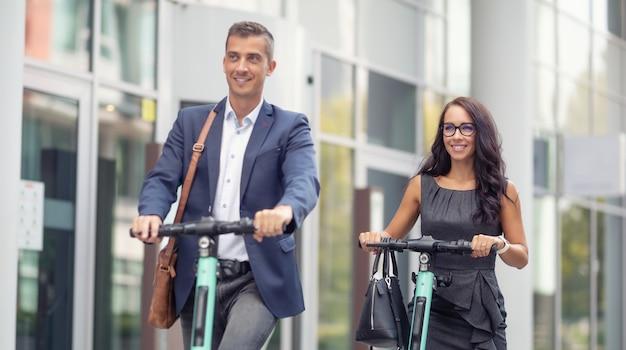 I dipendenti dell'ufficio si recano al lavoro in modo moderno, utilizzando scooter elettrici per la mobilità elettrica.