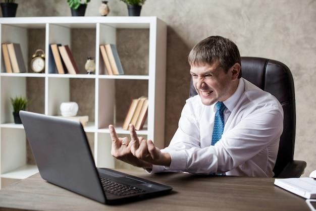Concetto dell'ufficio, di finanza, di internet, di affari, di successo e di sforzo - uomo d'affari arrabbiato che mostra il dito medio. negoziati senza successo.